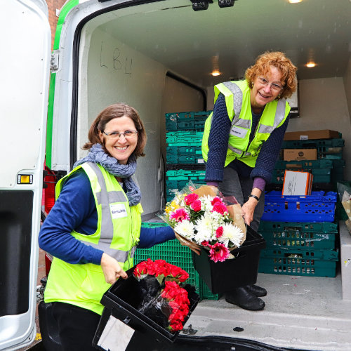 Volunteers Unloading Food And Flowers From A Felix Van